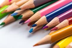 Verscheidene kleuren potloden op een Witboekblad Stock Foto's
