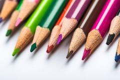 Verscheidene kleuren potloden op een Witboekblad Royalty-vrije Stock Afbeeldingen
