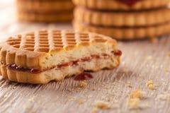Verscheidene koekjes met rode eigengemaakte marmelade op witte raad Stock Foto's