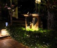 Verscheidene lantaarns verlichten de struiken, waarop de kleine witte bloemen bloeien Een olifants hoofdbeeldhouwwerk versiert de stock fotografie