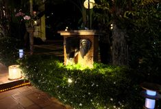 Verscheidene lantaarns verlichten de struiken, waarop de kleine witte bloemen bloeien Een olifants hoofdbeeldhouwwerk versiert de royalty-vrije stock fotografie