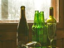 Verscheidene lege flessen alcohol dichtbij het vuile venster Selectieve nadruk Alcoholisme, dronkenschap, eenzaamheid en royalty-vrije stock afbeeldingen