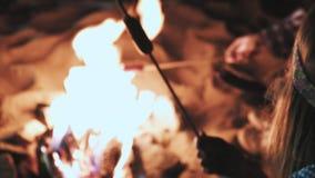 Verscheidene meisjes zitten door de brand bij nacht en gebraden gerechtworsten Bespreek en leid het gesprek Op een campagne zijn  stock video