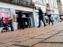 Verscheidene mensen die op de bestrating buiten een Gerenoveerde winkel lopen stock afbeeldingen