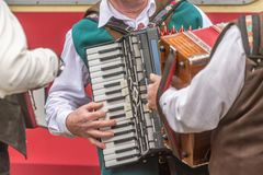 Verscheidene mensen in traditionele kleren spelen de harmonika stock foto's