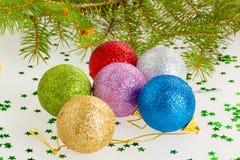 Verscheidene multicolored Kerstmisballen onder de boom Stock Afbeelding