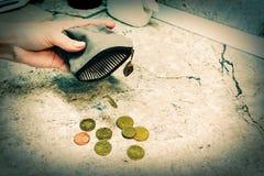 Verscheidene muntstukken vallen van een lege beurs in de hand van een vrouw royalty-vrije stock afbeeldingen