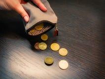 Verscheidene muntstukken vallen van een lege beurs in de hand van een vrouw royalty-vrije stock foto