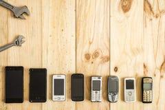 Verscheidene oude en nieuwe mobiele telefoons met staalmoersleutels stock afbeeldingen