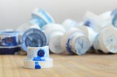 Verscheidene plastic pijpen van een verfspuitbus die op een houten oppervlakte tegen een grijze muurachtergrond liggen De kappen  stock foto's