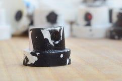 Verscheidene plastic pijpen van een verfspuitbus die op een houten oppervlakte tegen een grijze muurachtergrond liggen De kappen  stock afbeelding