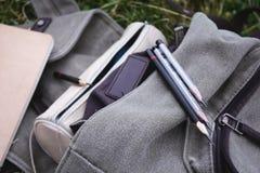 Verscheidene potloden op de grijze rugzak op het gras stock foto