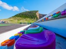 Verscheidene rijen van kleurrijke zetels in een stadion stock afbeelding