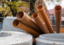 Verscheidene rioolpijpen liggen op de straat Stedelijk Landschap stock afbeeldingen