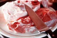 Verscheidene stukken van vers varkensvlees op de scherpe raad Stock Foto