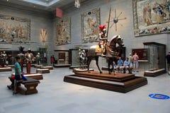 Verscheidene toeristen die rond ruimte met slagpantser, zwaarden en tapijtwerk, Cleveland Art Museum, Ohio, 2016 wandelen royalty-vrije stock foto's