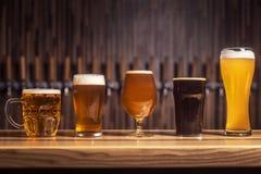 Verscheidene verschillende bieren bevinden zich op een rij bij de bar Stock Foto's