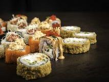 Verscheidene verschillende broodjes in de Japanse stijl op een donkere oppervlakte, zijaanzicht, met selectieve nadruk stock afbeelding