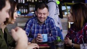 Verscheidene volwassen vrienden babbelen in het restaurant, het drinken Amerikaanse koffie, cappuccino en latte, wat zich op de l stock video