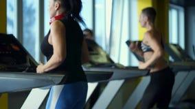 Verscheidene vrouwen lopen actief op een tredmolen in de geschiktheidsclub stock video
