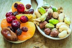 Verscheidenheden van droge vruchten en noten op houten lepels Stock Afbeelding