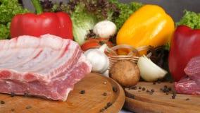 Verscheidenheden van ruw vlees op een scherpe raad met kruiden in kleine platen op de achtergrond van verse greens, divers ruw vl stock videobeelden