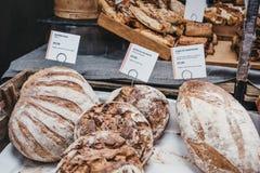 Verscheidenheid van artisanaal brood op verkoop bij een markt stock afbeelding