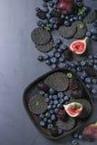 Verscheidenheid van bessen en fig. met zwarte crackers Stock Fotografie
