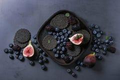 Verscheidenheid van bessen en fig. met zwarte crackers Royalty-vrije Stock Afbeeldingen