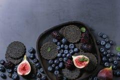 Verscheidenheid van bessen en fig. met zwarte crackers Stock Foto's