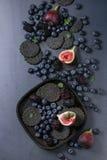 Verscheidenheid van bessen en fig. met zwarte crackers Royalty-vrije Stock Foto