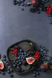 Verscheidenheid van bessen en fig. met zwarte crackers Stock Afbeelding