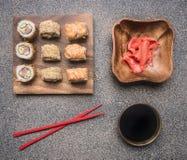 Verscheidenheid van broodjes op een houten plaat met sojasaus en gember, naast het zijn er rode eetstokjes, hoogste mening royalty-vrije stock foto's