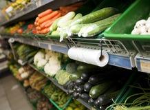 Verscheidenheid van groenten op planken in kruidenierswinkelopslag stock foto's
