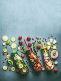 Verscheidenheid van kleurrijk gegoten water in flessen met vruchten bessen, komkommer, kruiden en drankstro met ingrediënten op l stock fotografie