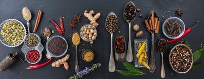 Verscheidenheid van kleurrijke kruiden en kruiden op zwarte steenachtergrond, hoogste mening, banner royalty-vrije stock foto's