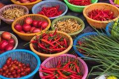 Verscheidenheid van kleurrijke peper, tomaten, gember en greens in manden voor verkoop bij lokale ochtendmarkt in Sattahip, Thail Stock Afbeeldingen
