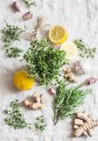 Verscheidenheid van kruiden en kruiden op grijze achtergrond - verse thyme en rozemarijn, kurkumawortel, knoflook en citroen De u Stock Foto's