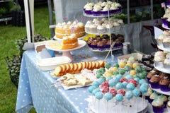 Verscheidenheid van luim cupcakes, lollys en andere cakes op vertoning op een marktkraam stock afbeelding