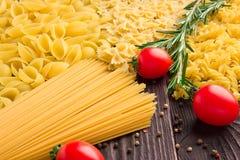 Verscheidenheid van soorten en vormen van droge macaroni met tomaten en rozemarijn Italiaans macaroni ruw voedsel of textuur: dee stock afbeeldingen