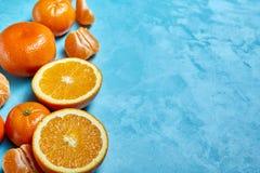 Verscheidenheid van verse citrusvruchten voor het maken van sap of smoothie over blauwe geweven achtergrond, hoogste mening, sele Royalty-vrije Stock Afbeeldingen