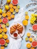 Verscheidenheid van verse citrusvruchten voor het maken van sap of smoothie met verse croissants en sap op een lichtblauwe achter Stock Foto's