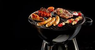 Verscheidenheid van vlees die op een draagbare barbecue roosteren Stock Foto