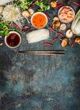 Verschieden vom Asiaten, der Bestandteile und Soßen mit Essstäbchen auf rustikalem Hintergrund, Draufsicht, Platz kochend für Tex stockfotografie