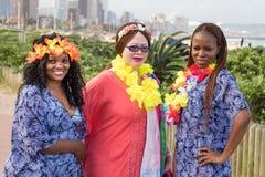 Verschiedenartigkeit: Drei Frauen, zwei Schwarze und ein Weiß, die zusammen in der Ufergegend von Durban, Südafrika feiern stockbilder