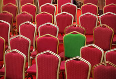 Verschiedenartigkeit oder einzigartiges Konzept - grüner Stuhl in einer Gruppe Rot eine lizenzfreies stockbild