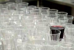 Verschiedenartigkeit, Satz leere Gläser mit einem einzelnen vollen Glas stockbilder