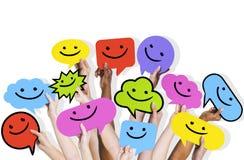Verschiedenartigkeits-Hände, die Smiley Faces Icons Concept halten Stockbilder