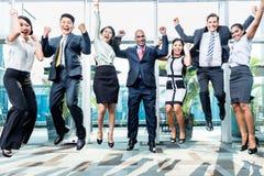 Verschiedenartigkeitsgeschäftsteam, das Erfolg feiernd springt Lizenzfreie Stockfotografie