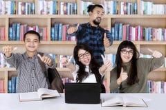Verschiedenartigkeitsstudenten mit den Daumen oben in der Bibliothek Stockfotografie